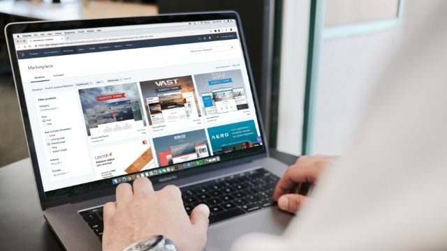 A man looking at a laptop screen showing website design templates