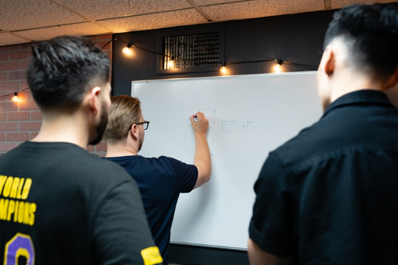 Val, Luis, and Evan from Free Logic working at a whiteboard