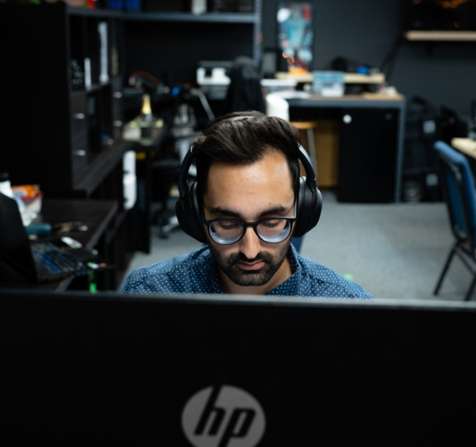Nikhil from Free Logic working at a computer while wearing headphones
