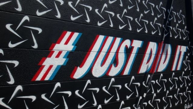 A wall showing Nike's custom hashtag #JustDidIt to build brand awareness.